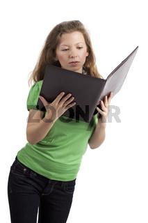 Stehende junge Frau liest in einer Akte