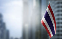 A small flag of Thailand on the background of a blurred background