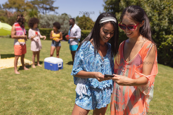 Two mixed race female friends using smartphone at a pool party