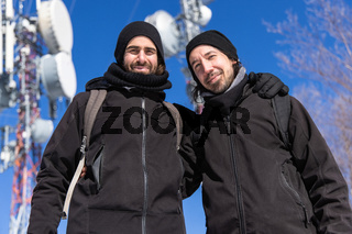 Tourists pose in front of communication towers