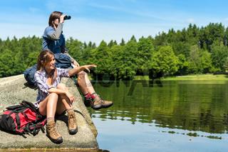 Teenage hikers birdwatching at lake