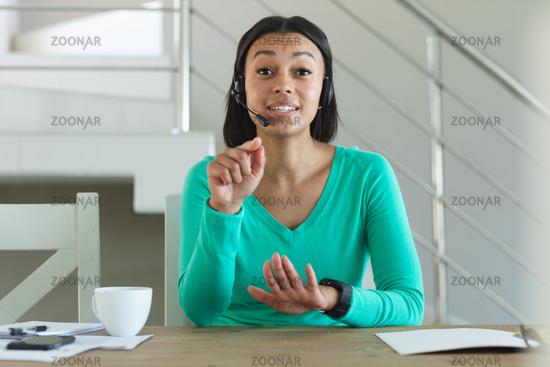 Portrait of african american woman wearing phone headset having a video call at home