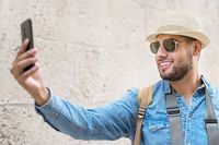 Happy tourist taking selfie in old city