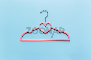 Black Friday or clothing industry concept on blue background with pink hanger
