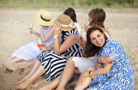 Cheerful women proposing toast on beach