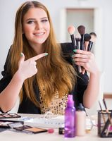 Young woman applying make-up preparing for party