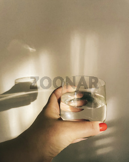Female hand holding glass of pure clean mineral water against beige wall with shadow