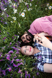 Romantic couple love moment in field among wild flowers