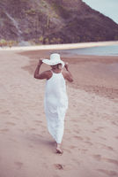 Woman on beach in white dress and hat