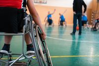 the selector of the basketball team with a disability stands in front of the players and shows them the stretching exercises before the start of training