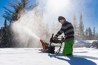 Young man removing snow with mechanical snowplough