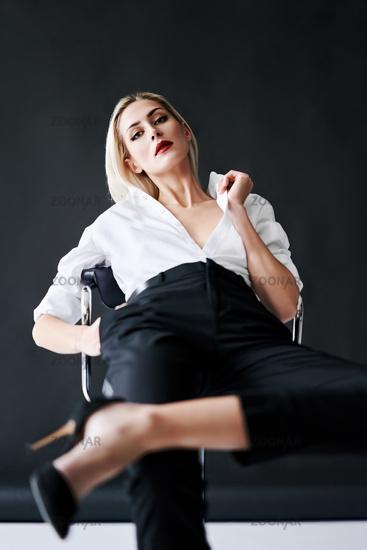 Fashion portrait of daring trendy woman posing on black studio background