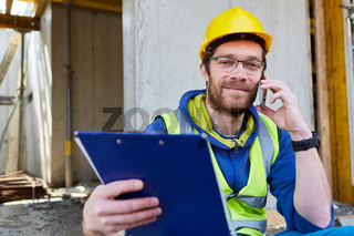 Handwerker auf Baustelle beim Telefonat mit Checkliste