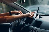 Navigator in car vehicle transportation commuter. Driver man using mobile phone navigator app while driving car