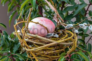 Osterei in einem Nest aus Zweigen