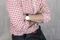 Torso of young entrepreneur wearing plaid shirt casualy leaning on desk with arms crossed against gray background wall.
