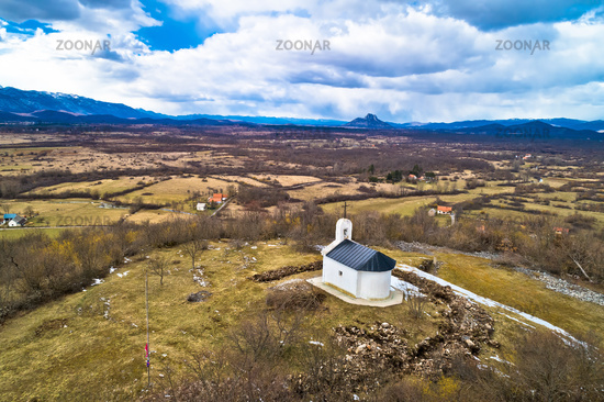 Lika region. Church on the hill in Lovinac and Velebit mountain in Lika landscape aerial view