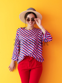 Portrait of young woman wearing sunglasses and hat over a yellow background