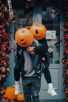 Guy giving his girlfriend a piggyback ride. Both with pumpkin heads