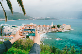 Smartphone in the hands with a photo against the background of the old town in Montenegro