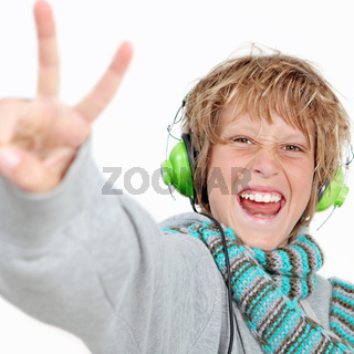happy kid doing v sign and listening to music wearing headphones.