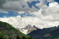 High rocky mountains with snow and glacier, sunlit blue sky with clouds at summer evening