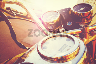 Fragment of old fashioned motorcycle with handlebar and dashboard in sunlight