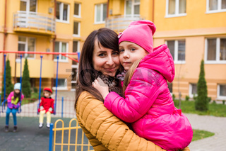 Mother with girl at playground. Woman holding she