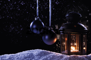laterne im schnee mit christbaumkugeln