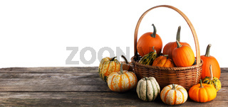 Basket with pumpkins on wooden table
