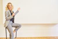 Junge Business Frau mit Mikrofon bei einer Präsentation