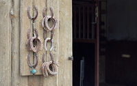 Old worn horseshoes displayed on wall of stables