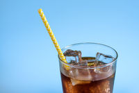 A glass of cola with ice on blue background