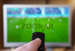 hand pointing remote control at tv with soccer or football match