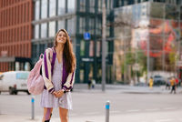 Playful portrait of pretty young woman, having fun at the street.