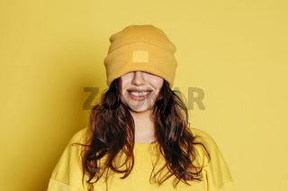 Cheerful woman in yellow outfit and hat