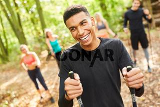 Lachender junger Mann beim Nordic Walking