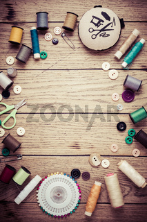 Sewing and craft tools - threads and buttons on wooden background in vintage style with free space for text