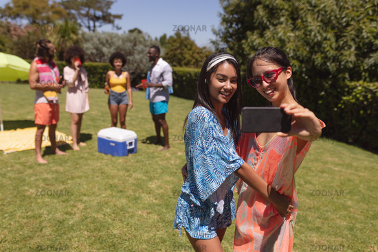 Two mixed race female friends taking selfie at a pool party