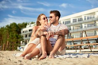 happy couple sitting on summer beach