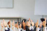 Geschäftsleute halten Daumen hoch bei der Arbeit