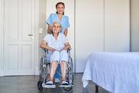 Altenpflegerin schiebt Seniorin nach Schlaganfall im Rollstuhl