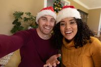 Two happy diverse female and male friends in santa hats having video call at christmas time