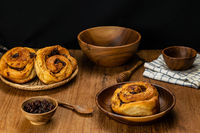 Homemade delicious raisin cinnamon cake roll in wooden plate and in bamboo tray.
