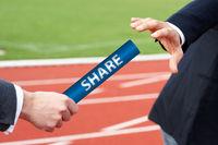 Businessman passes share baton in stadium relay race social media concept