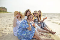 Cheerful women with rose wine resting on beach