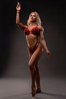 Powerful blond female model with glittering bikini in dark