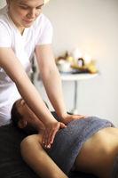 Crop masseur massaging body of woman