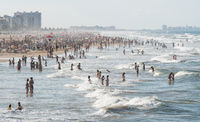 Many people in stormy ocean with high waves and at the beach of Gandia, Spain