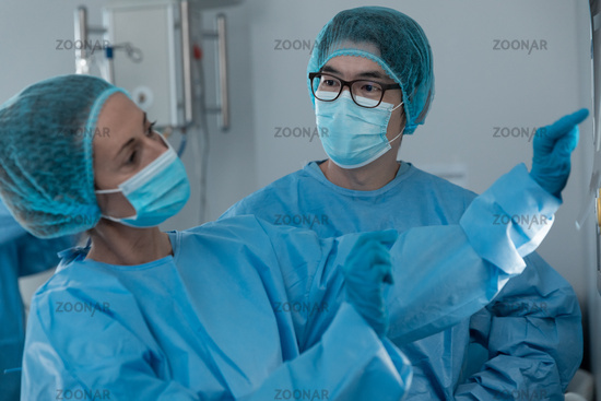 Diverse couple of male and female surgeons in operating theatre wearing face masks looking at screen